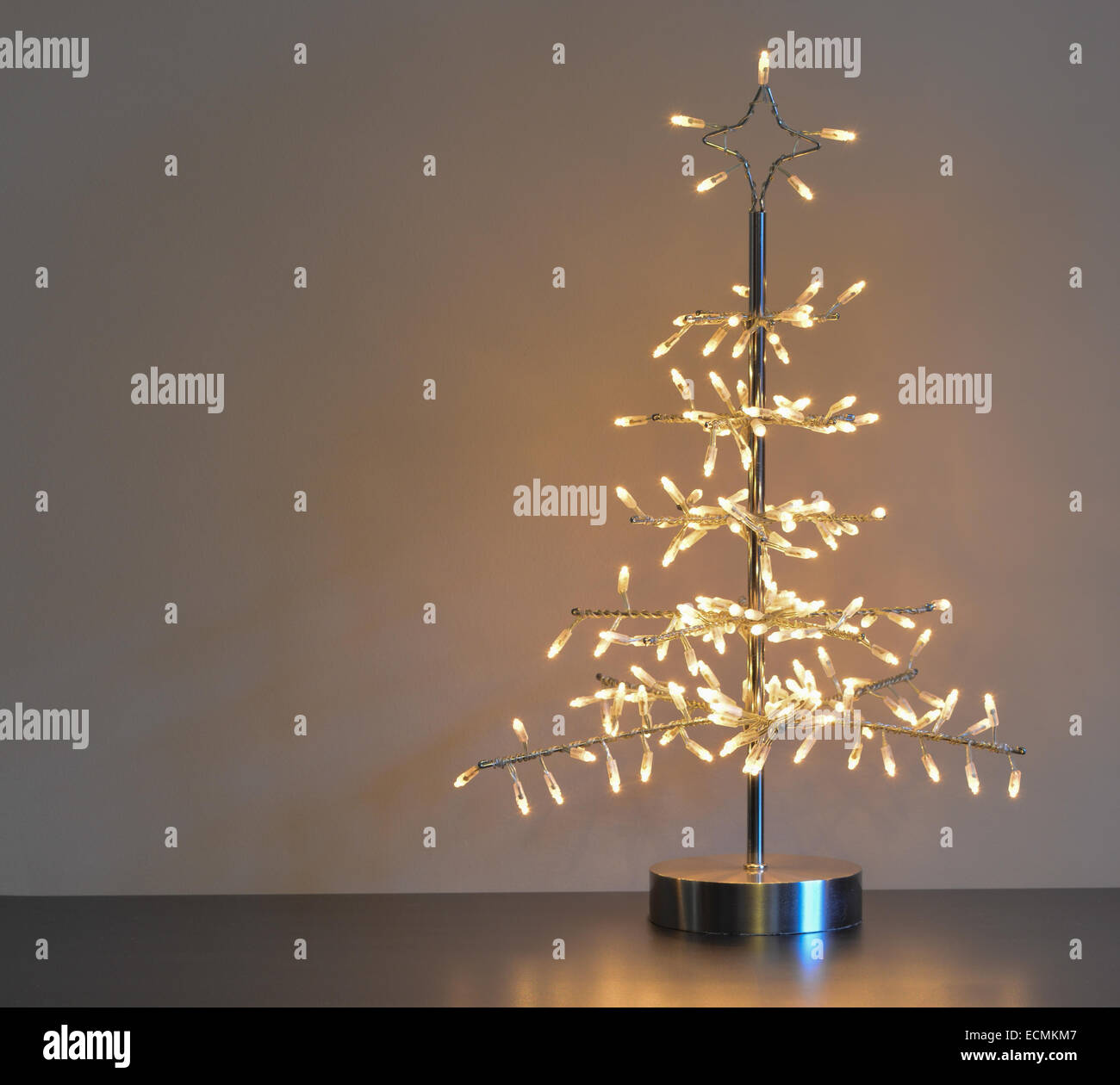 stylised silver metal and wire christmas tree with white lights neutral background and left copy