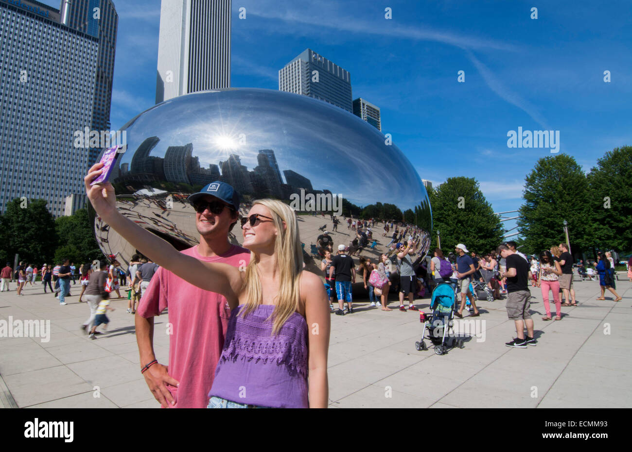 Chicago Illinois Millennium Park with famous Cloud Gate sculpture The Bean with skyline in background skyscrapers - Stock Image