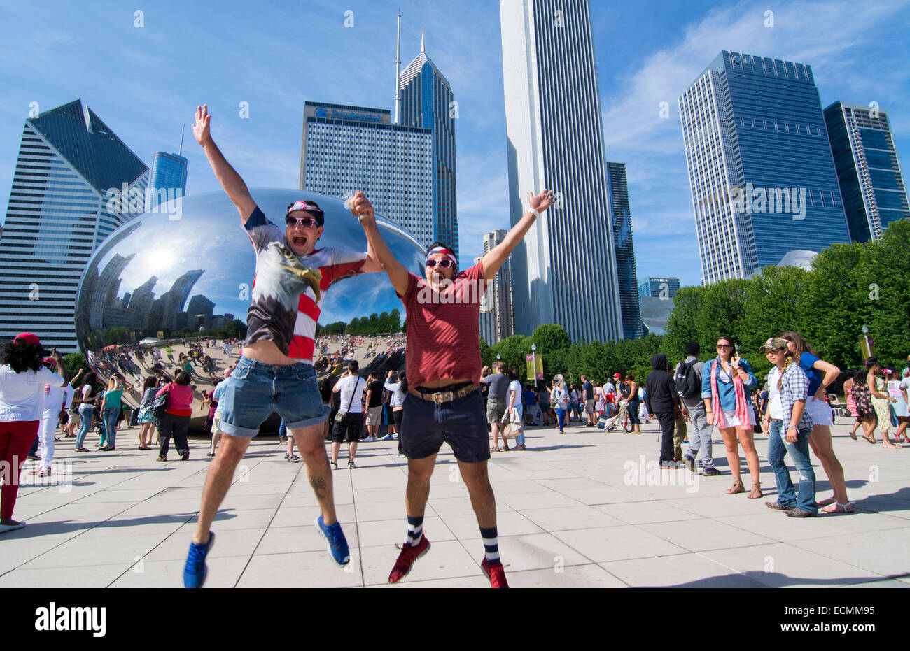 Chicago Illinois Millennium Park July 4th locals jumping for joy at Cloud Gate sculpture called The Bean with skyline - Stock Image