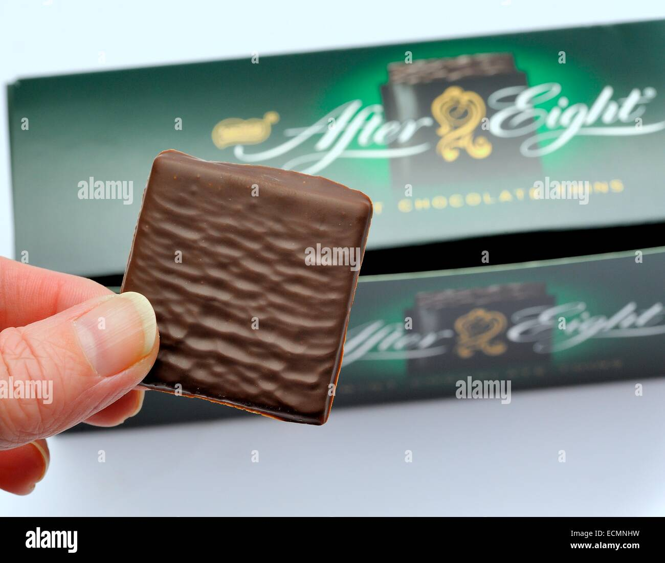 An After eight chocolate mint being held above the out of focus box - Stock Image