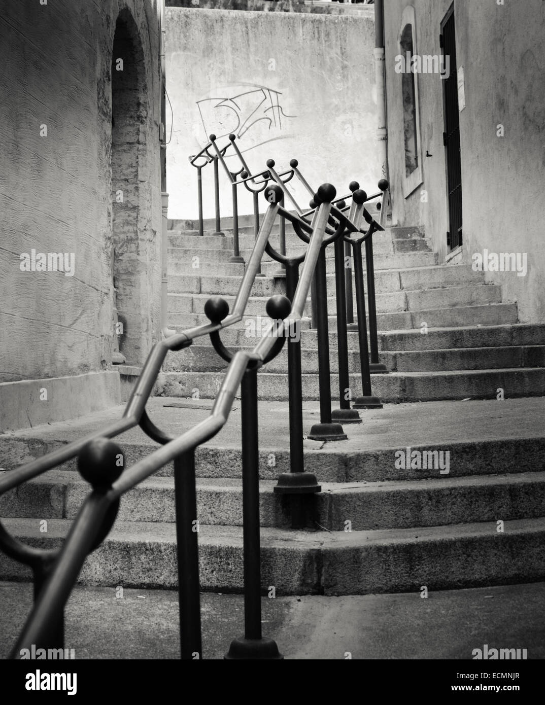 Metal hand rails lead the eye up stone steps to graffiti in the papal town of Avignon, Provence, France - Stock Image