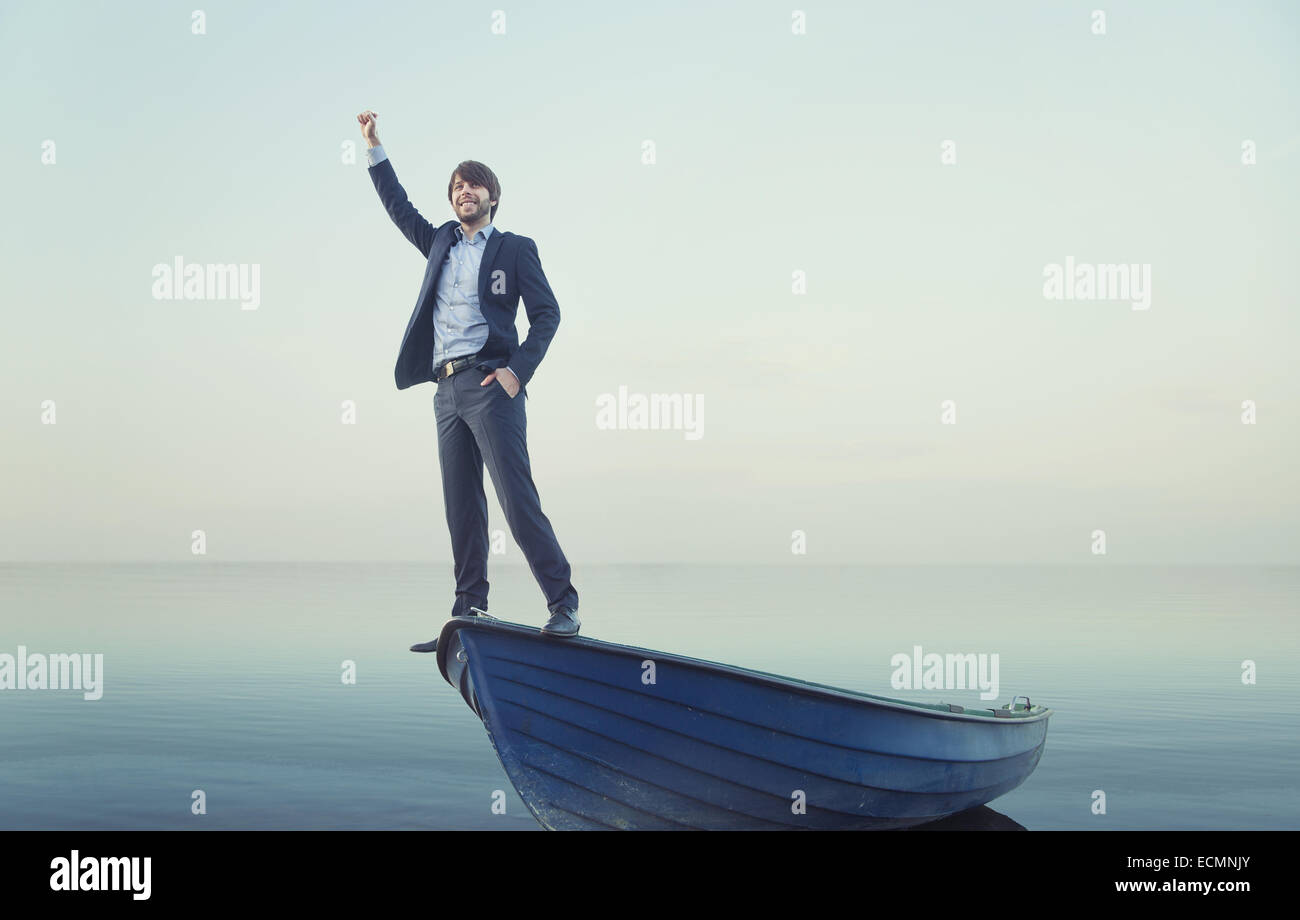 Cheerful young guy on the tiny boat - Stock Image
