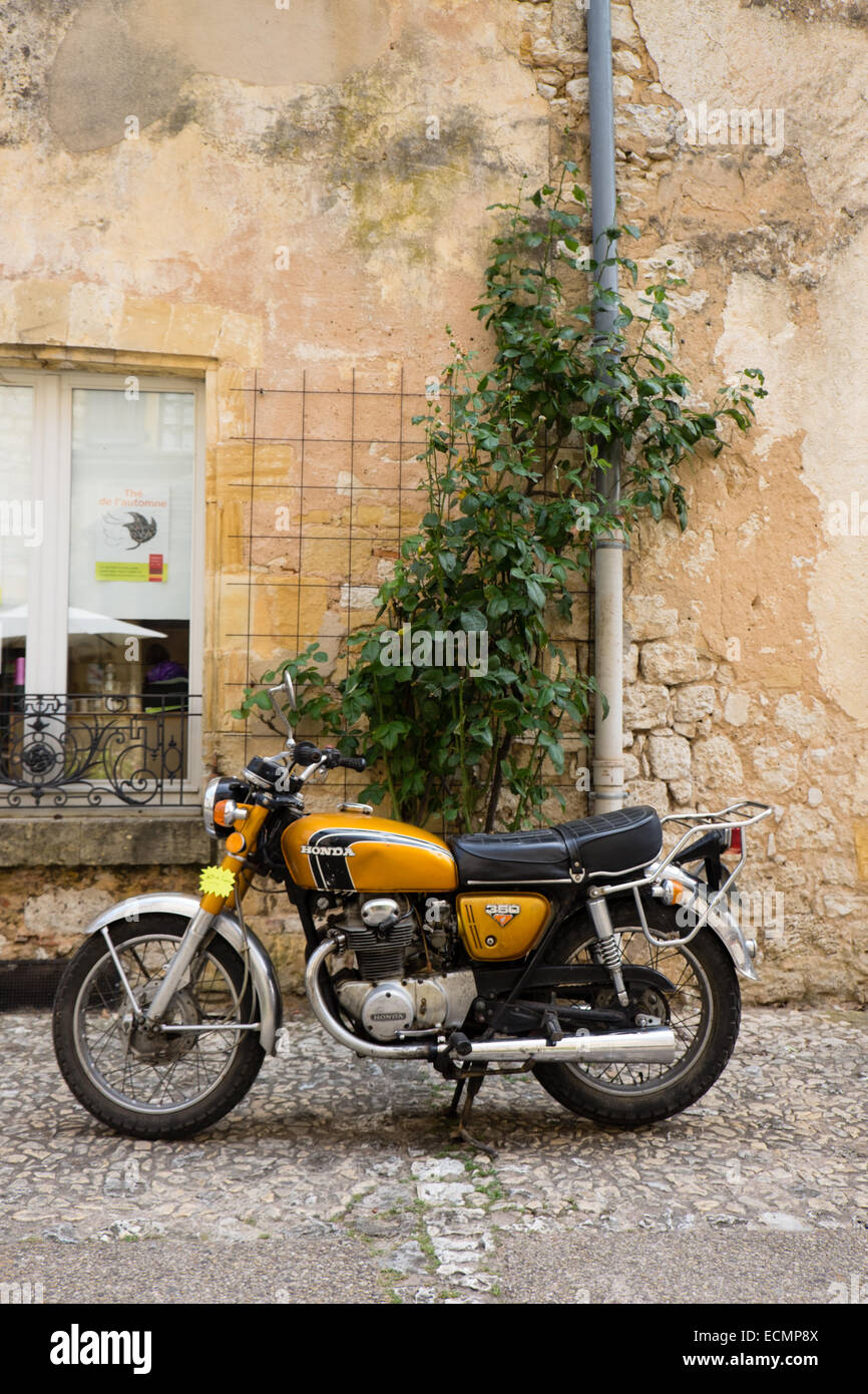 A 1970s gold coloured Honda CB350 stands before a decrepit honey coloured wall in the French Bastide town of Monpazier. - Stock Image