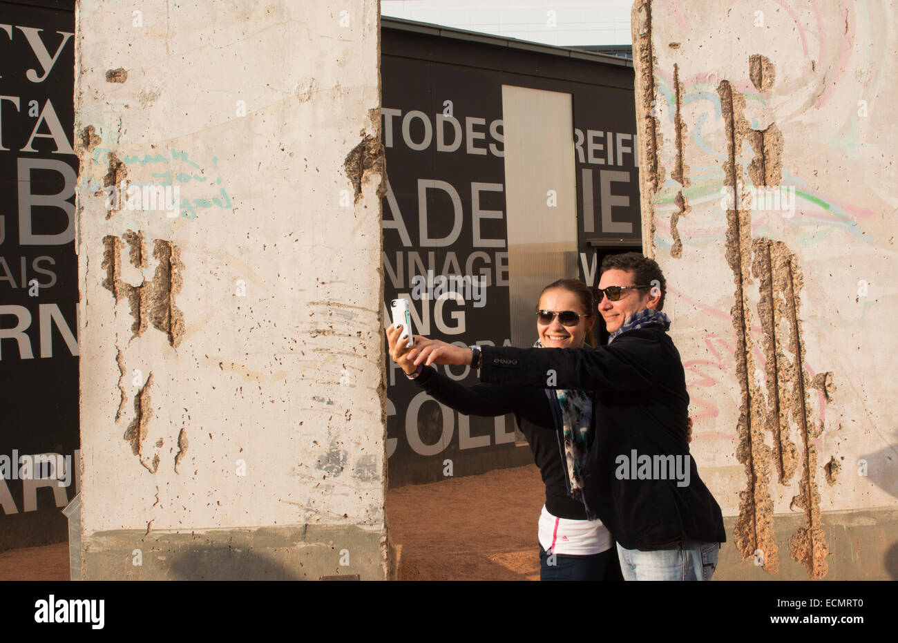 Berlin Germany Checkpoint Charlie museum Berlin Wall pieces tourist couple from Spain taking picture selfie  MR - Stock Image