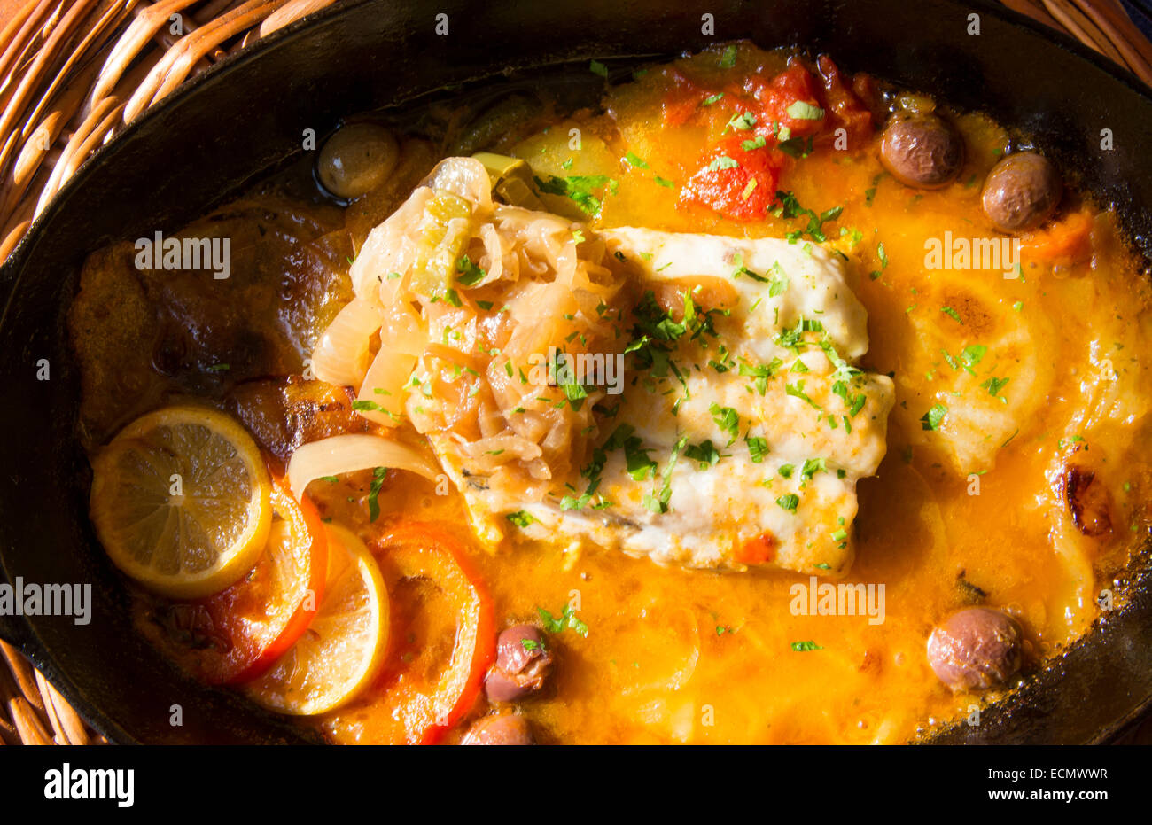 Barcelona Spain food plate of seafood Hale fish with beautiful lighting  in hot dish - Stock Image