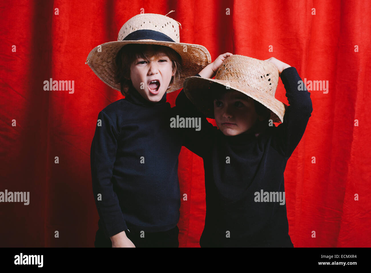 Studio portrait of two boys wearing black clothes and a straw hat - Stock Image