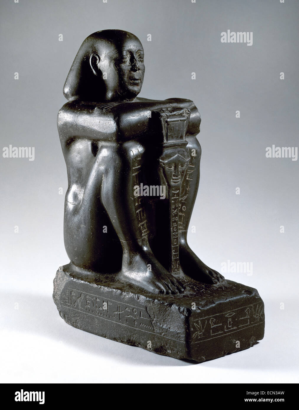 Block statue of Harsomtusemhat (664-610 B.C.) sitting on a socle, with his legs grouped and the hands on his knees. Stock Photo