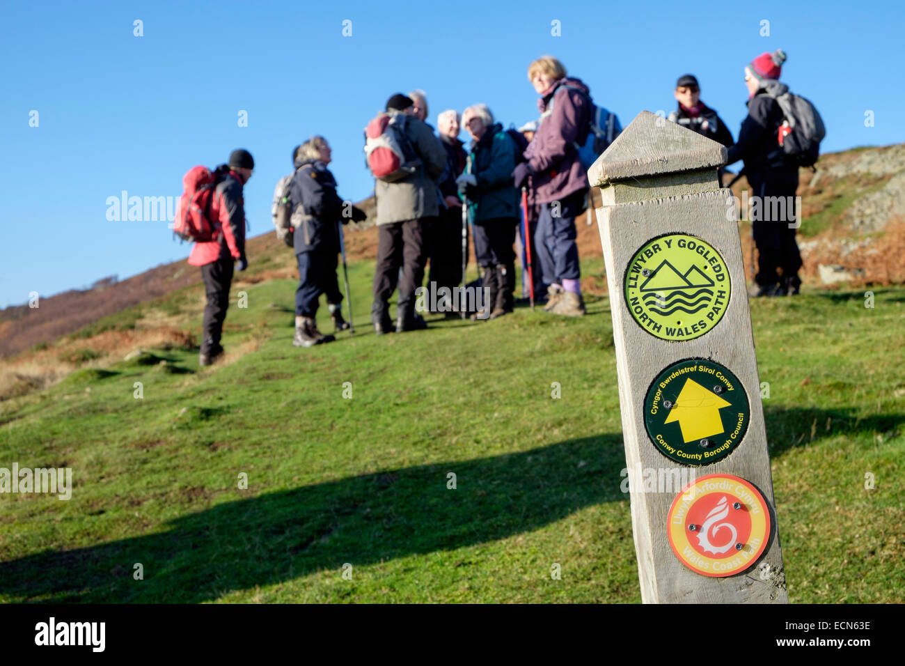North Wales coast path sign with a group of Ramblers on Conwy Mountain in Snowdonia National Park. Conwy Wales UK - Stock Image