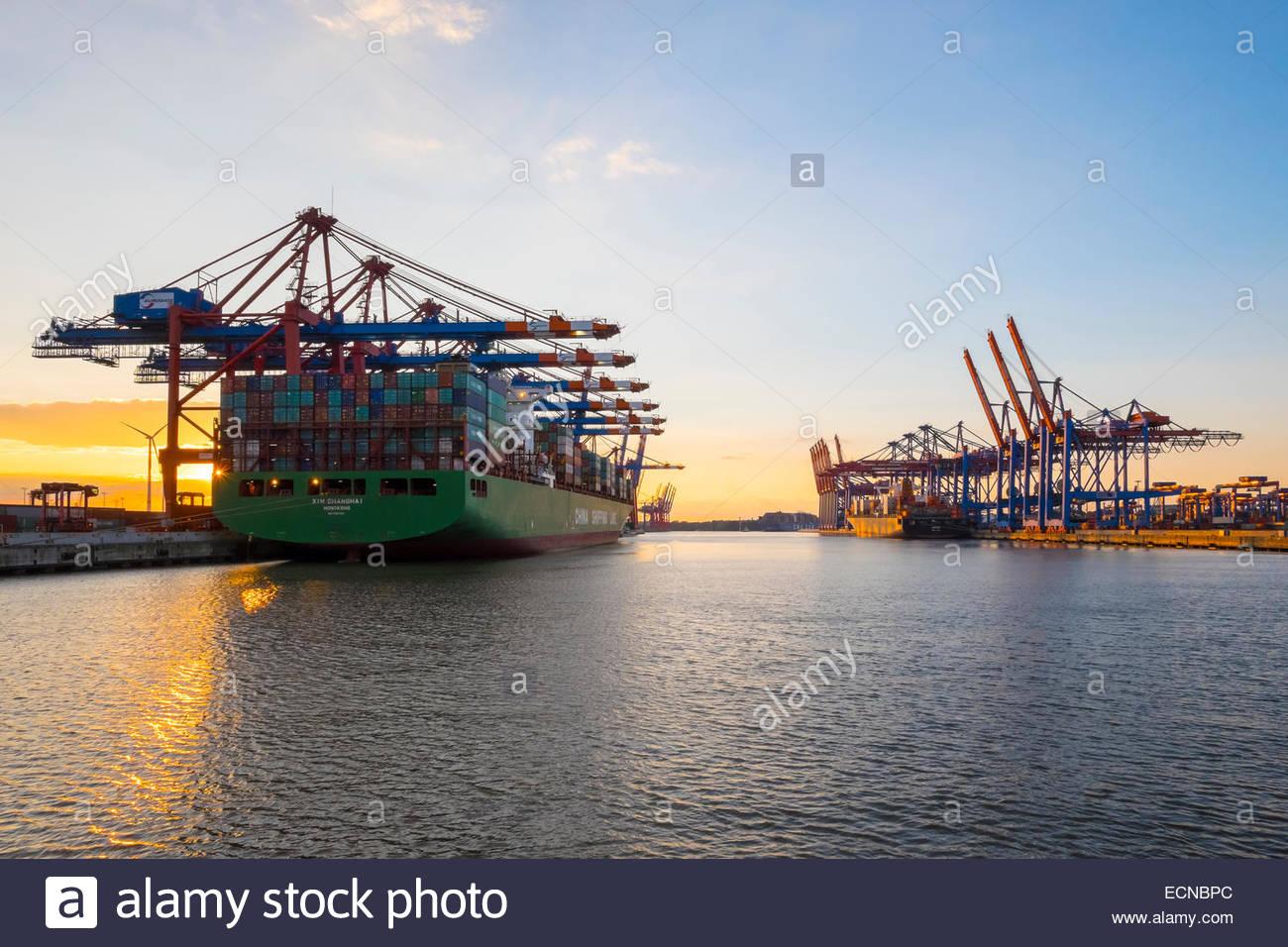 Cargo ships being loaded at Eurokai and Burchardkai in Hamburg Harbor at sunset, Waltershofer Hafen, Hamburg, Germany - Stock Image