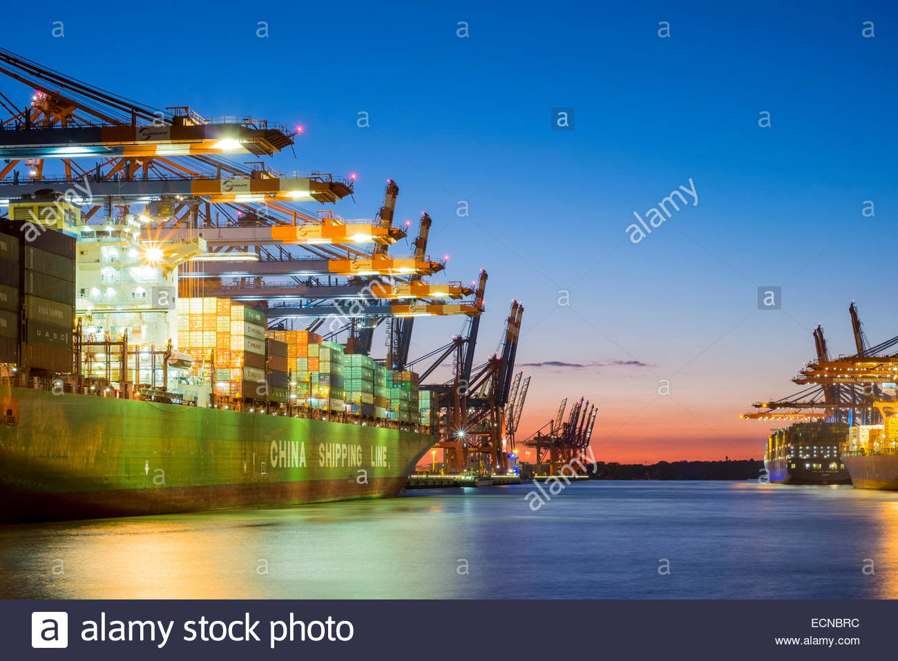 Cargo ships being loaded at Eurokai and Burchardkai in Hamburg Harbor at night, Waltershofer Hafen, Hamburg, Germany Stock Photo