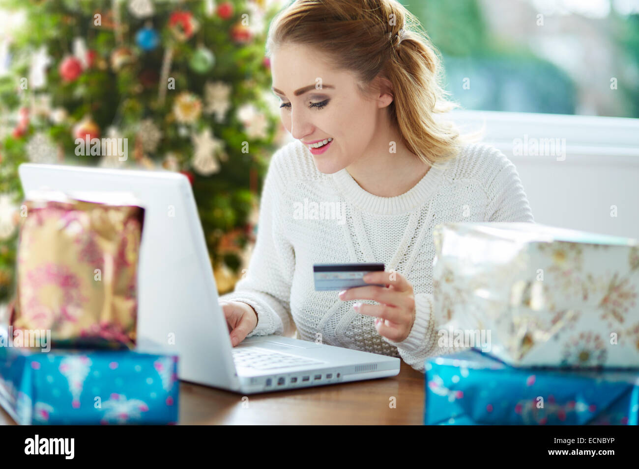 Woman shopping online at Christmas - Stock Image