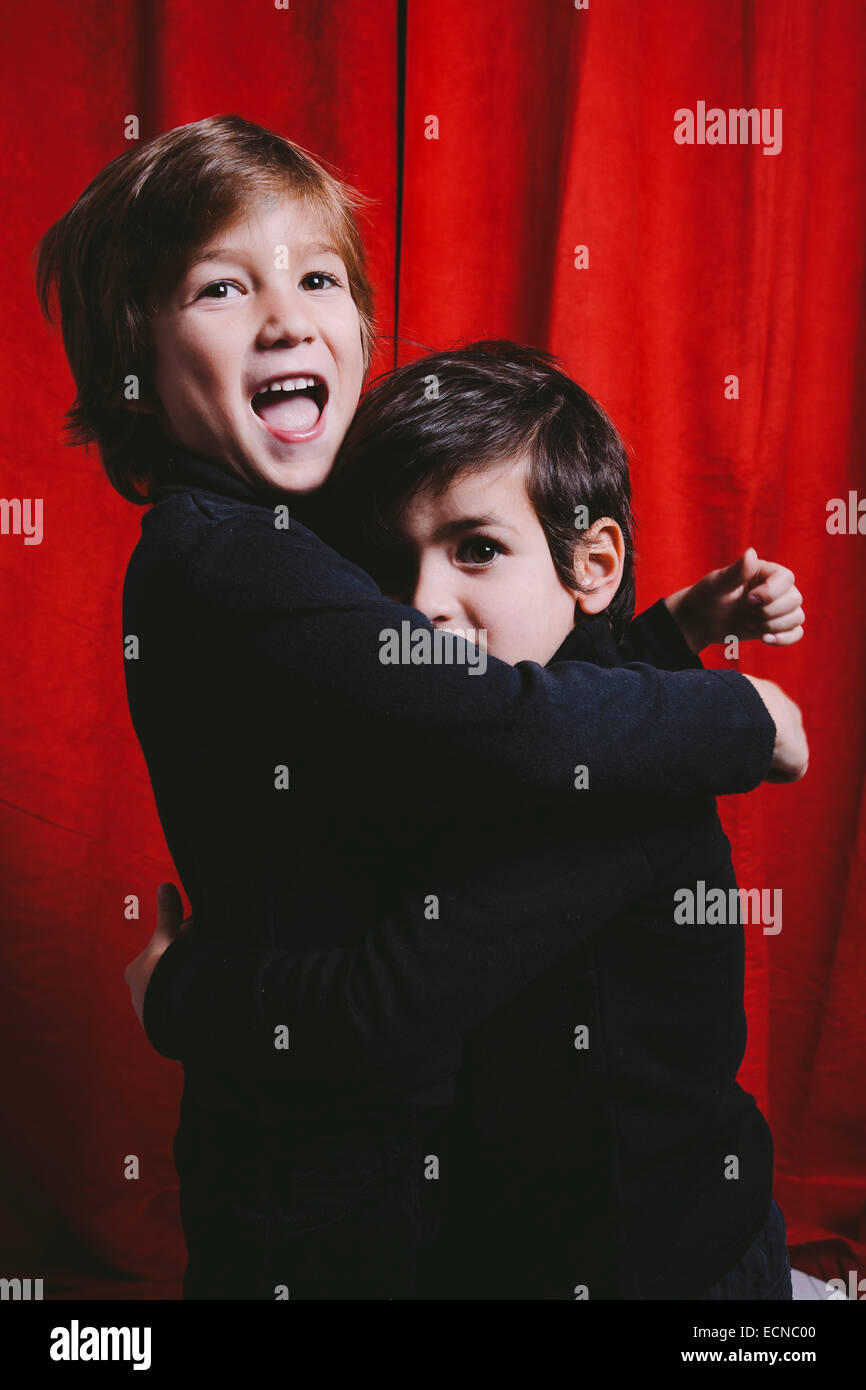 Studio portrait of two boys wearing black clothes on a hug - Stock Image