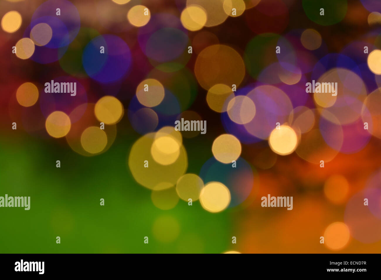 Blurred 'New Year' Christmas tree lights background in warm colours of gold green purple and orange - Stock Image
