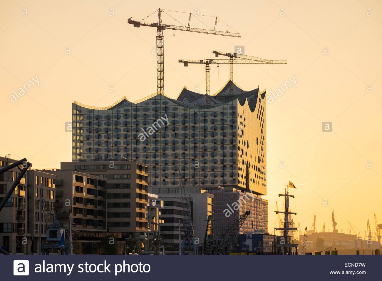 Under-construction Elbphilharmonie (Elbe Philharmonic Hall) and buildings on Kaiserkai at sunset, HafenCity, Hamburg, - Stock Image