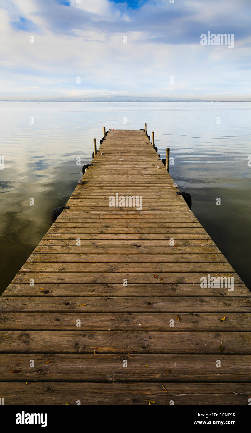Wooden jetty perspective onto lake without people - Stock Image