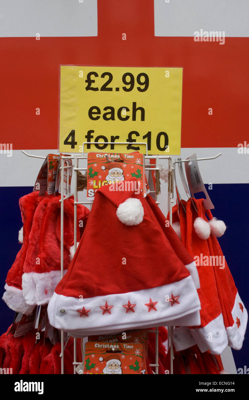 In the week before Chrsitmas, santa hats on sale outside a tourist trinket shop in London's West End. Each one - Stock Image