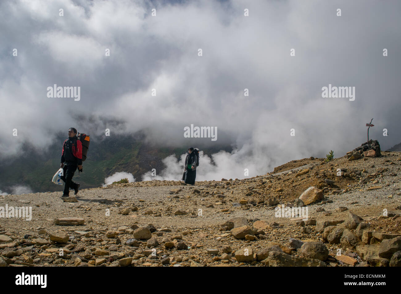 Local climbers walk along caldera ridge of Mount Papandayan. - Stock Image
