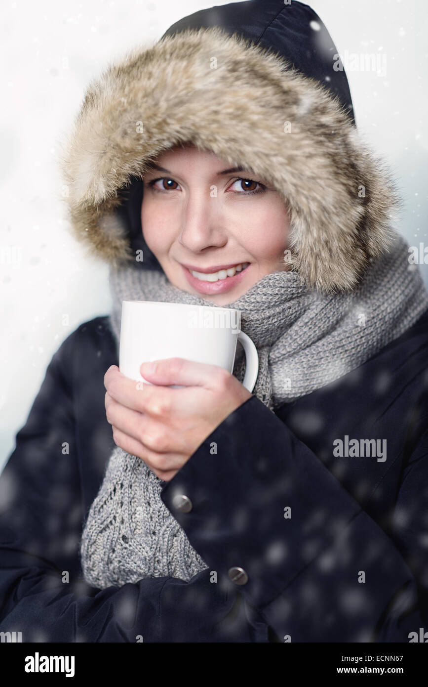 Pretty young woman in warm winter fashion bundled up warmly in a thick coat, knitted scarf and fur hat clasping - Stock Image