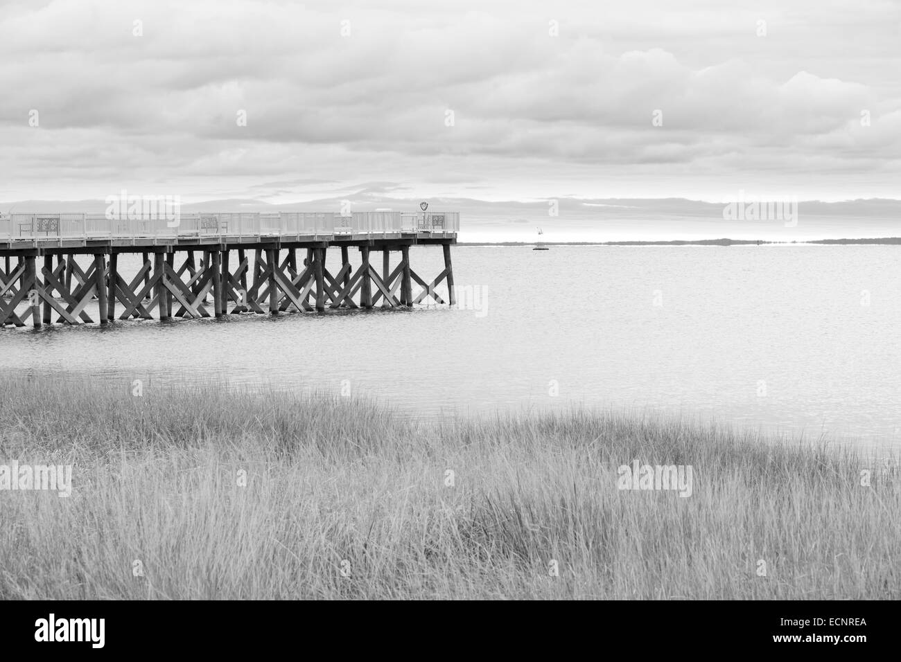jetty on edge of harbor on overcast day, black and white. - Stock Image