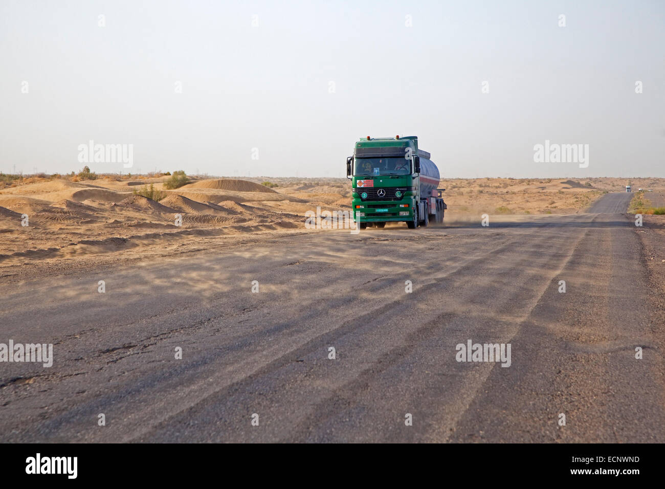 Truck crossing the Karakum desert in Turkmenistan and wind blowing sand from the dunes over the road - Stock Image