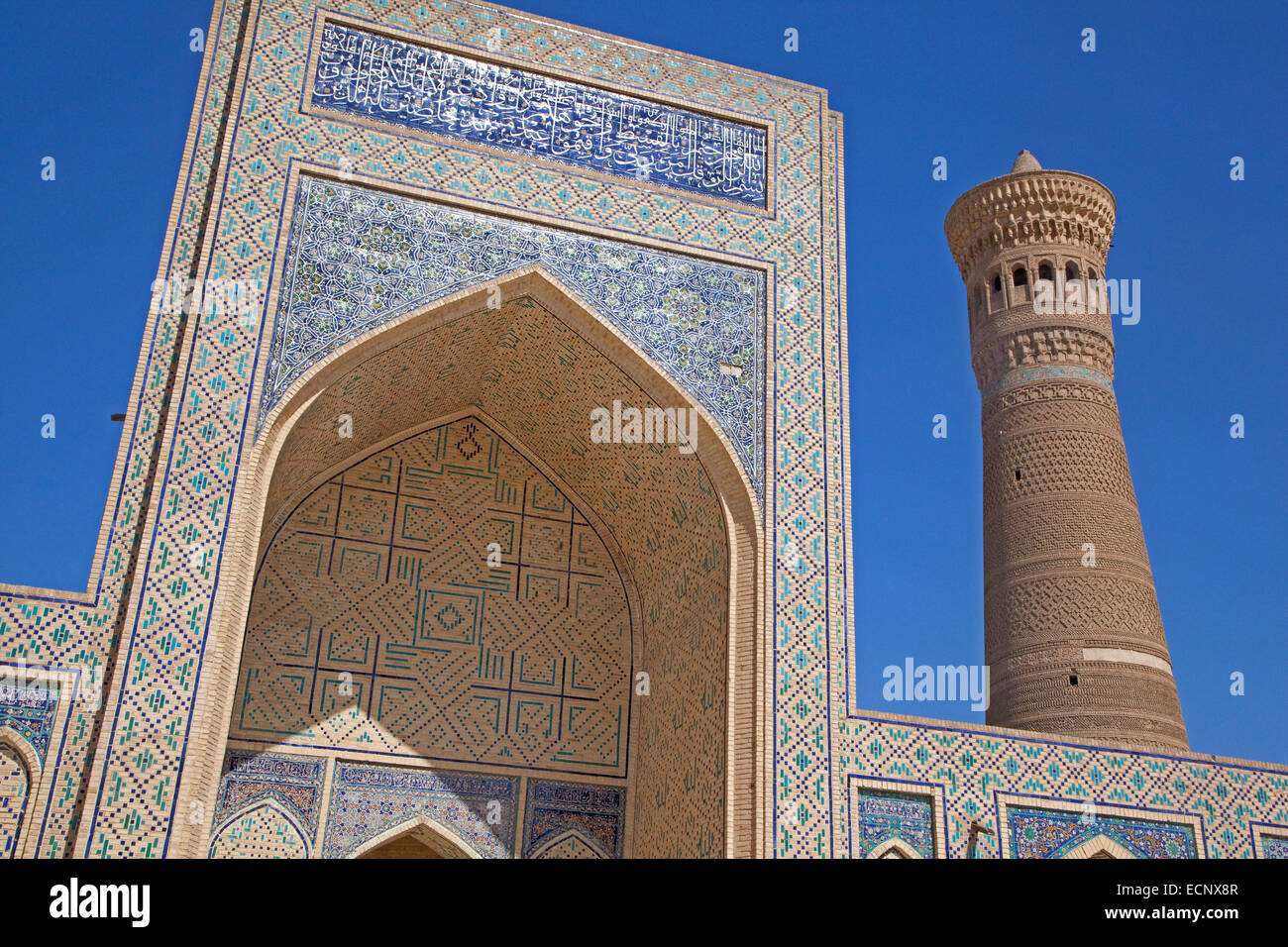 Tiled Iwan portal and brick minaret of the Kalyan Mosque, part of the Po-i-Kalyan Complex in Bukhara, Uzbekistan - Stock Image