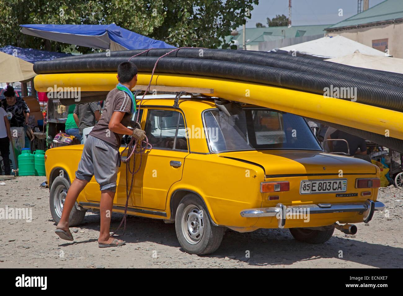 Uzbek boy fixing large pipes on top of old Trabant in Uzbekistan - Stock Image