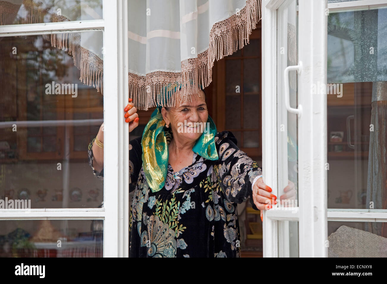 Smiling Uzbek elderly woman showing golden teeth and orange finger tips dyed with henna at home, Samarkand, Uzbekistan - Stock Image