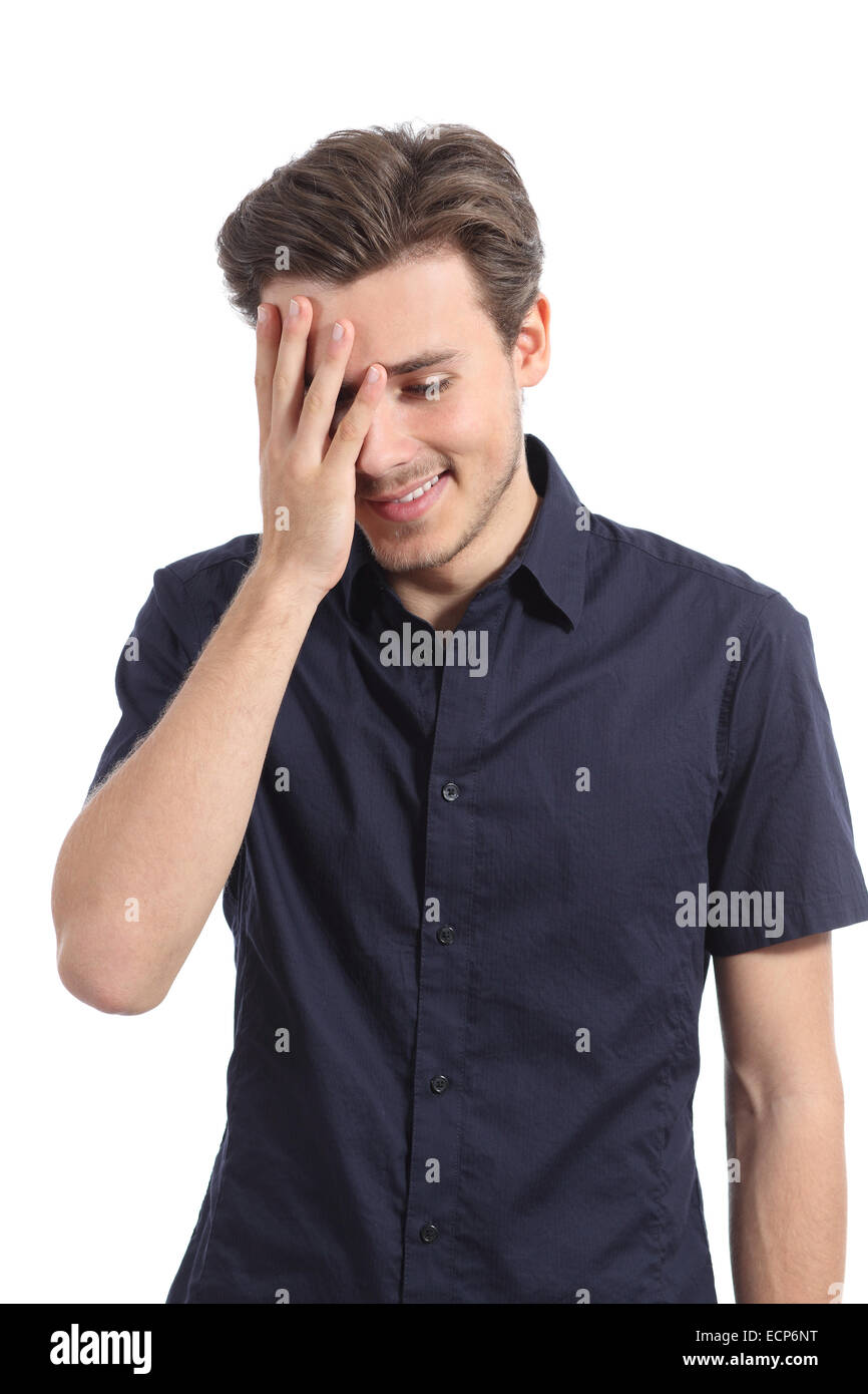Ashamed man smiling covering his face with a hand isolated on a white background - Stock Image