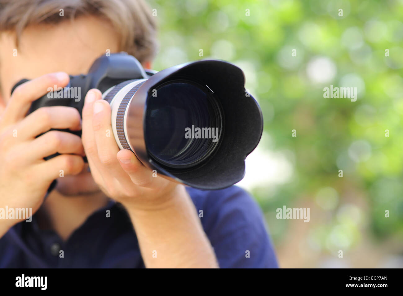 Close up of a photographer using a dslr camera with a green background - Stock Image