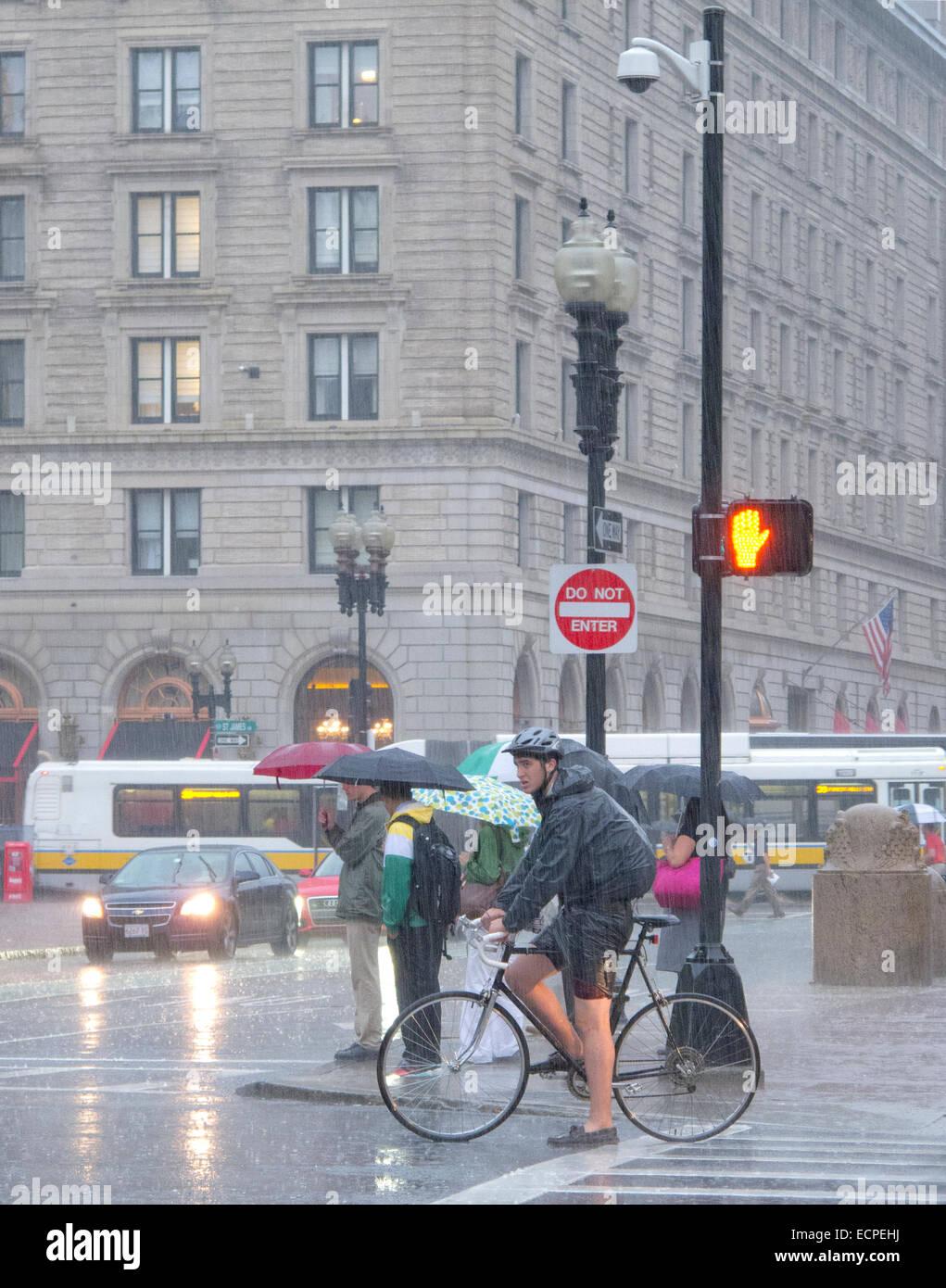 A cyclist waits at a boston traffic light in the rain Stock Photo