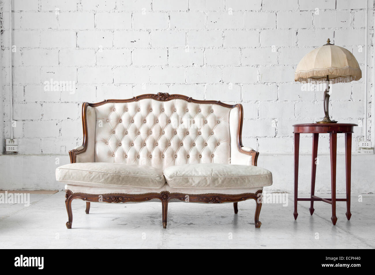 White genuine leather classical style sofa in vintage room with desk