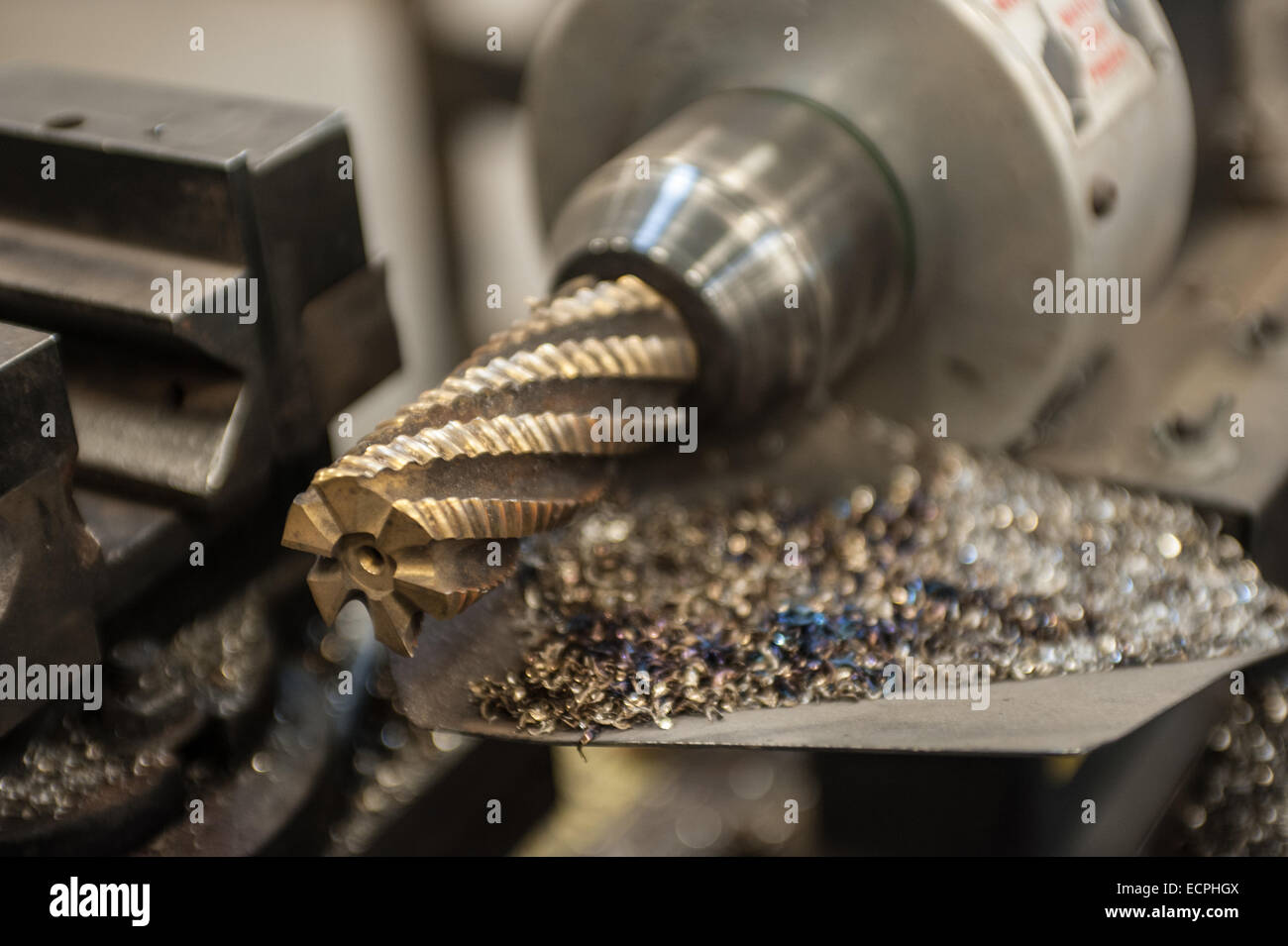Steel grinder for coping round handrails with steel shavings located in a miscellaneous metal shop. - Stock Image