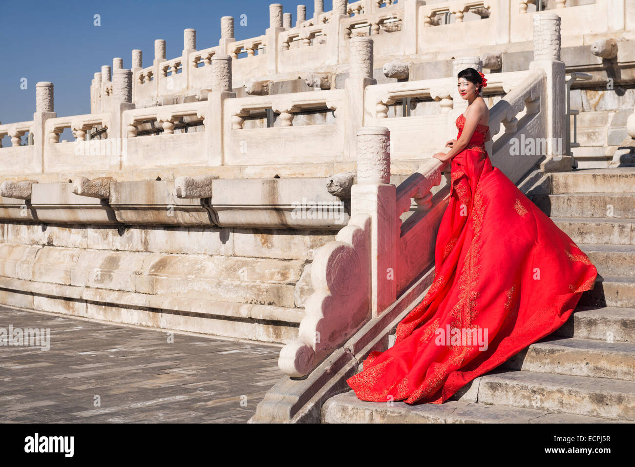 7cdecb68a Young bride in red wedding dress in front of The Temple of Heaven in  Beijing,