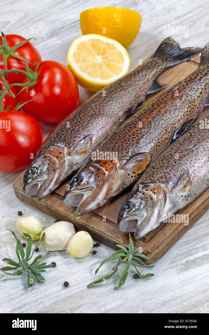 Vertical image of fresh wild trout being prepared, skin coated with oil, for cooking on server board. Herbs, tomatoes, - Stock Image