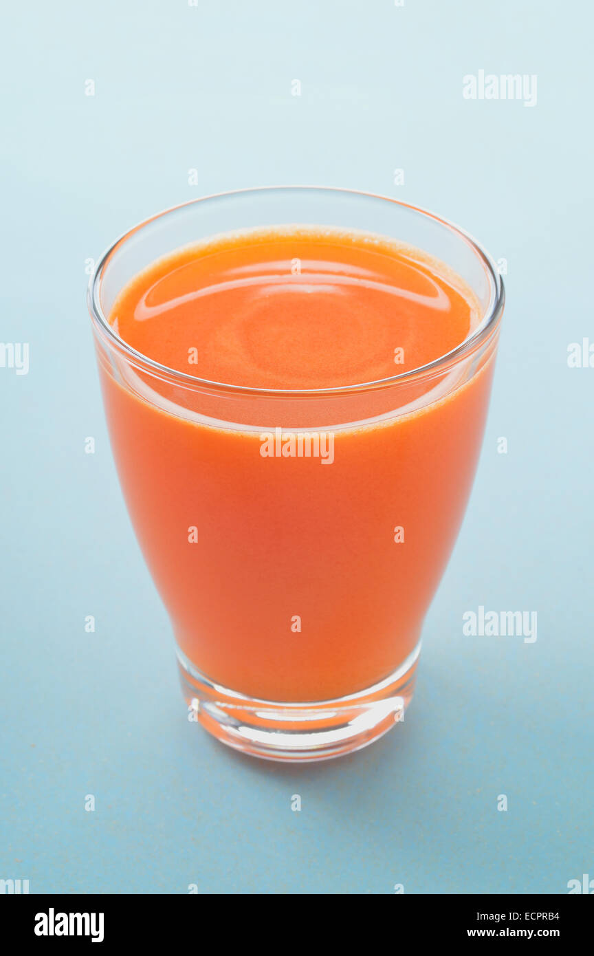 Carrot and apple freshly pressed juice in glass on light background. Healthy raw vegetable and fruit drink for healthy - Stock Image