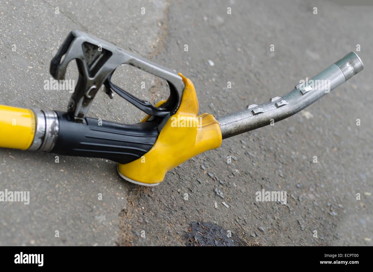 Yellow gas nozzle on the sidewalk - Stock Image