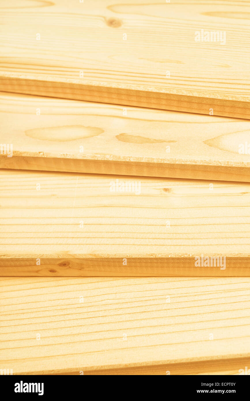 Pine planks stacked and ready for some carpentry job or woodworks. Close up with selective focus and shallow depth - Stock Image