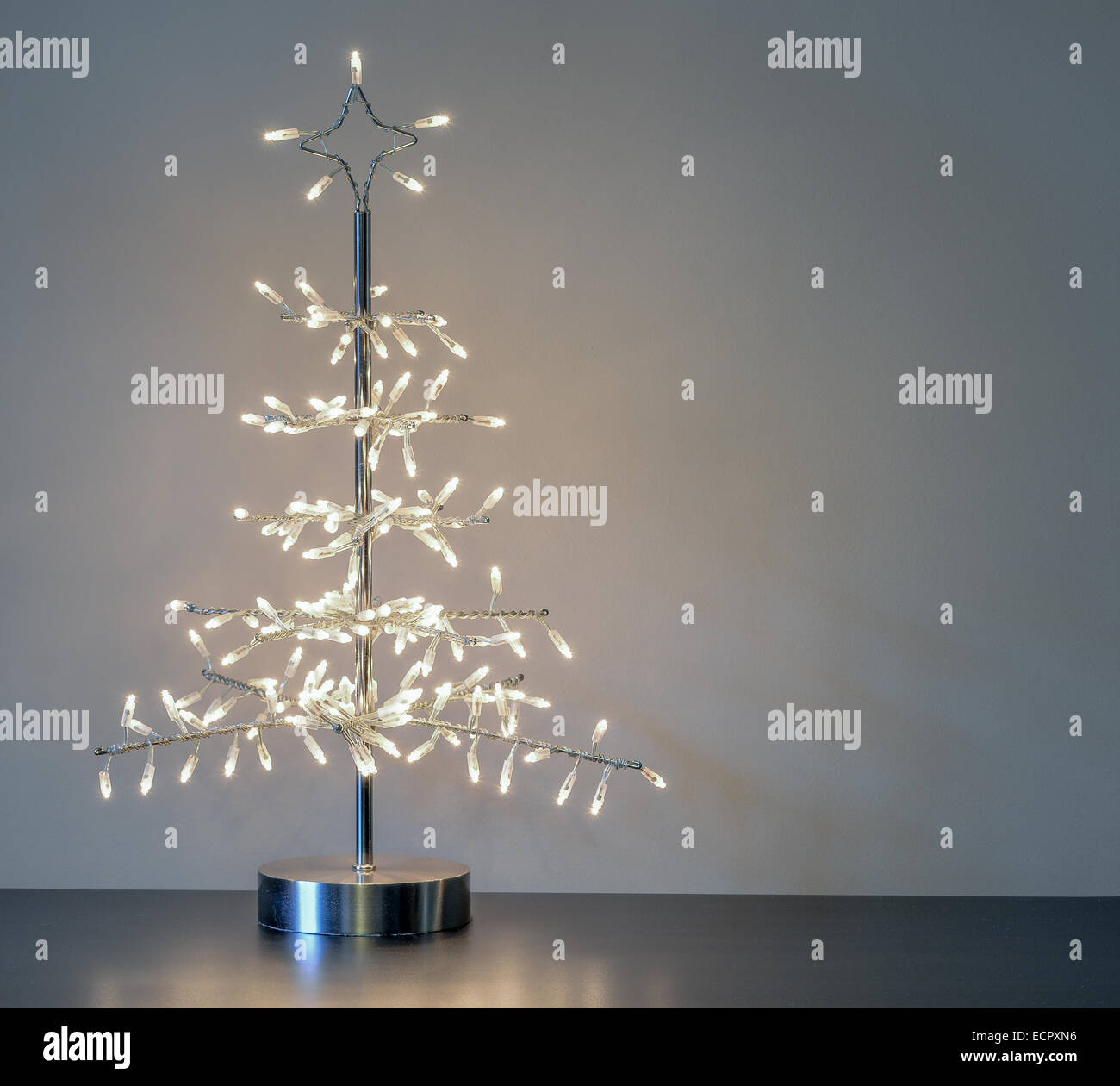 silver metal minimalist Christmas Tree ornament with white lights against plain neutral background with copyspace - Stock Image