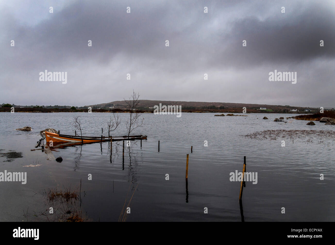 Lake Meela, Dungloe, County Donegal, Ireland. 18th December, 2014. Waterlogged fishing boat and overcast sky give - Stock Image