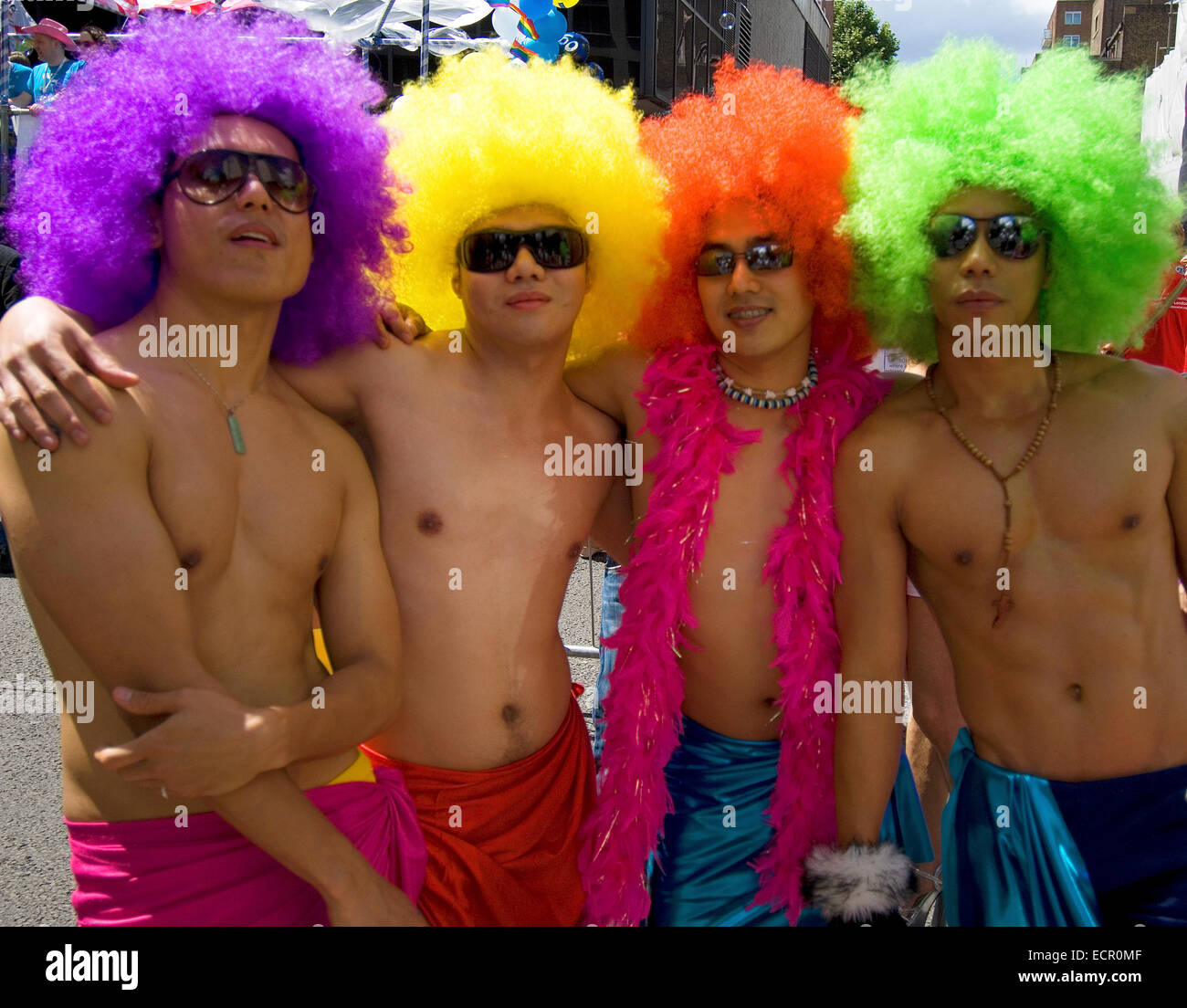 Four friends in colourful wigs pose before the start of the Pride in London Parade. - Stock Image