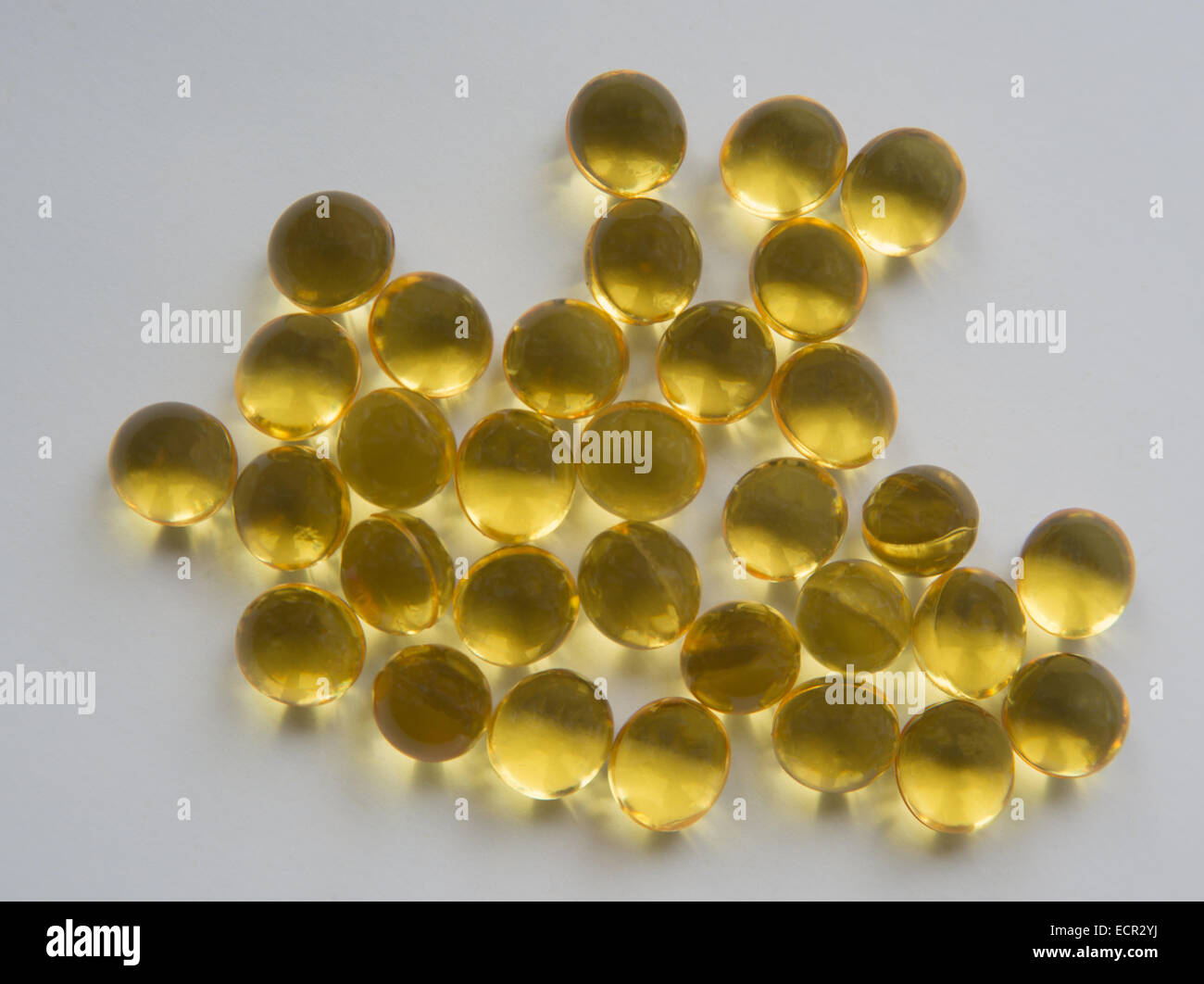 Many transparent yellow pills (capsule) are situated on the white background. - Stock Image