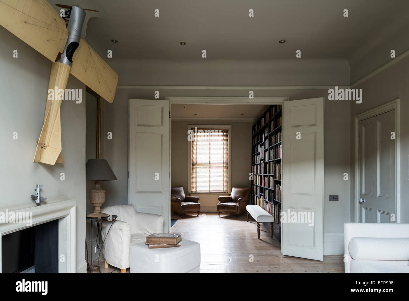 Large scale model airplane hung above fireplace in spacious living room with double doors and white sofa - Stock Image