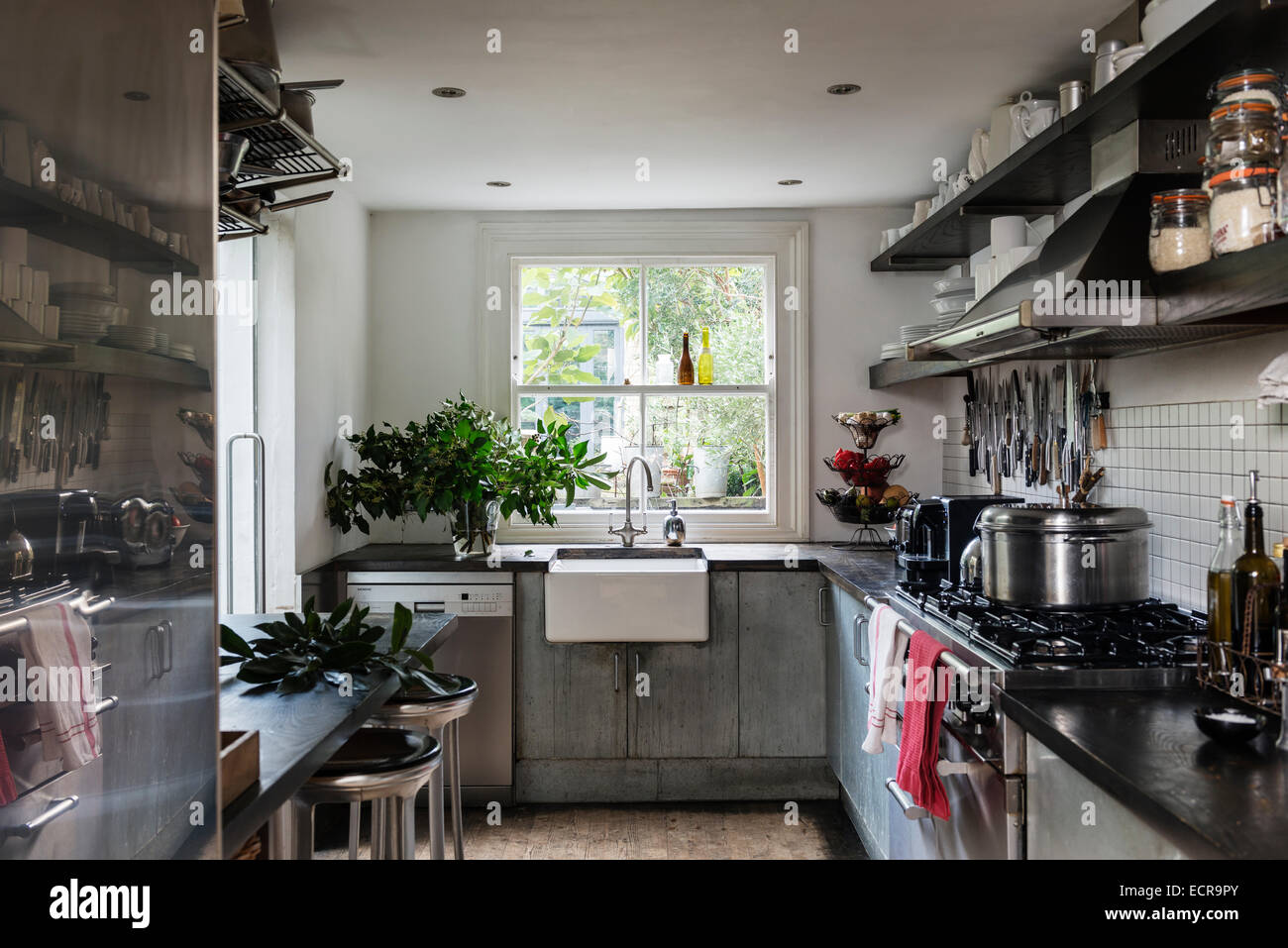 Contemporary kitchen with belfast sink, breakfast bar and open shelving - Stock Image