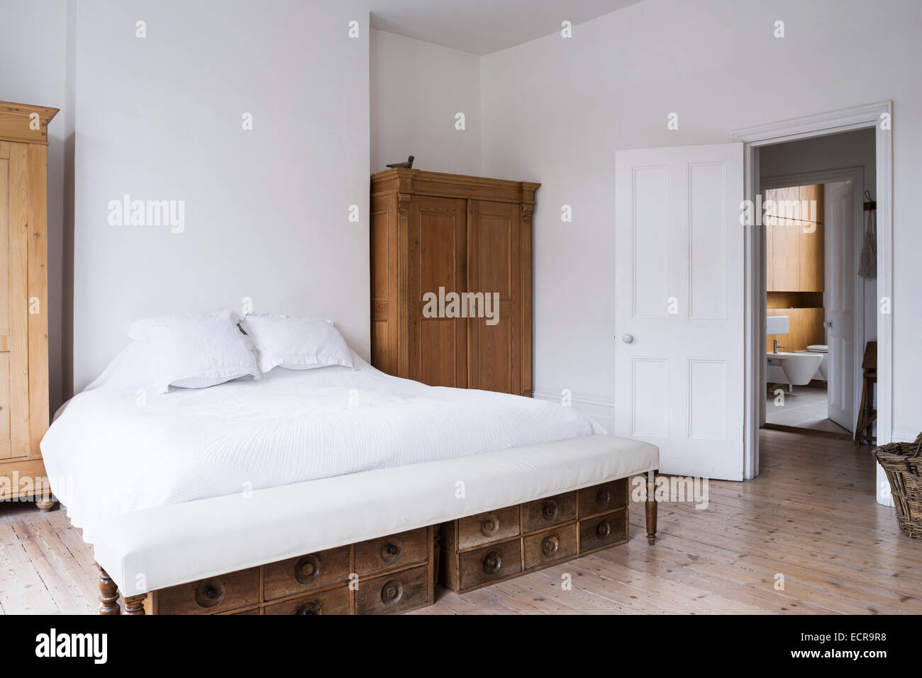 Large white bed in minimal white bedroom with wooden wardrobes and flooring - Stock Image