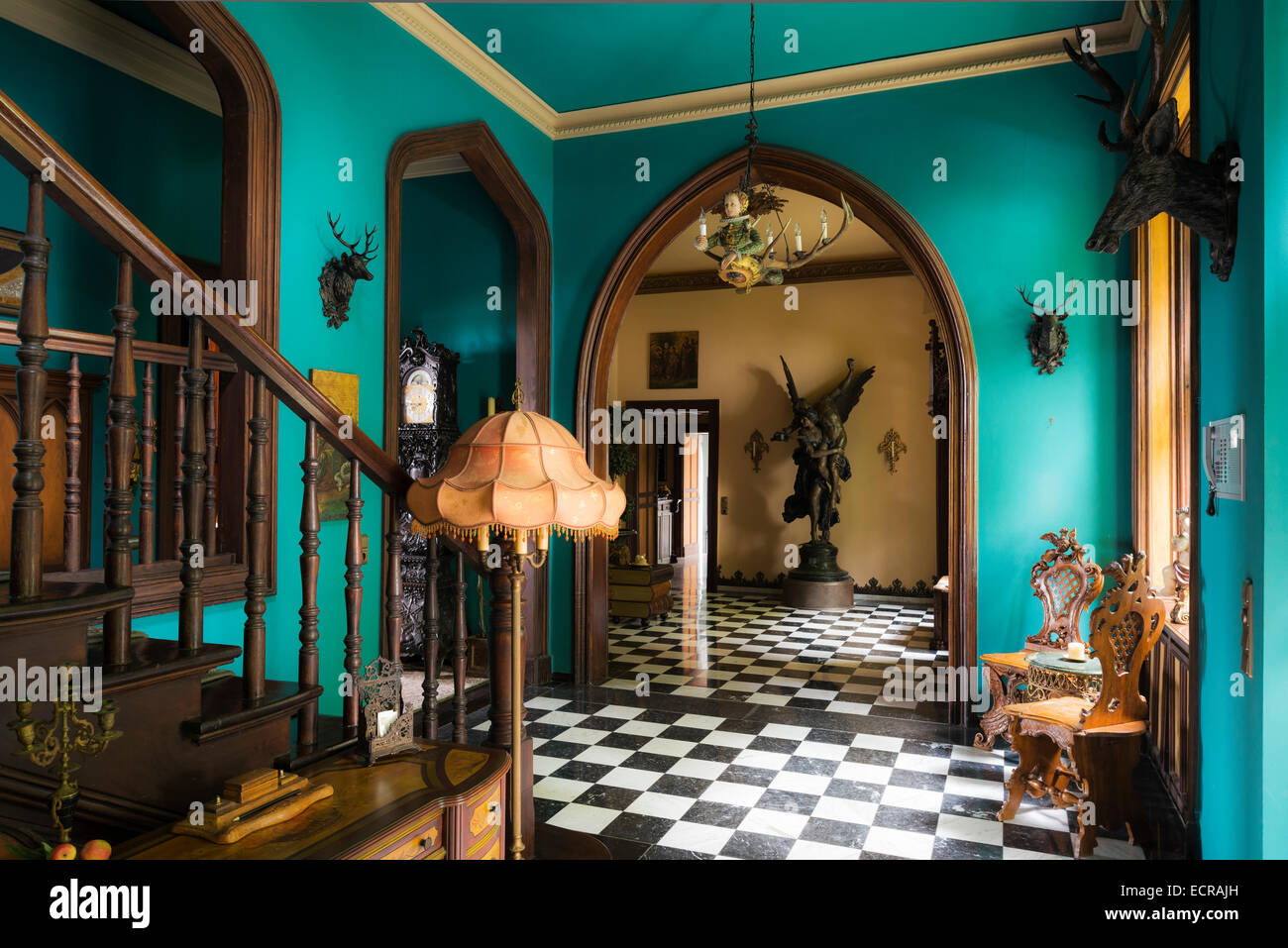 Chequered marble floor in entrance hall of castle with arched doorways and bronze sculptures - Stock Image