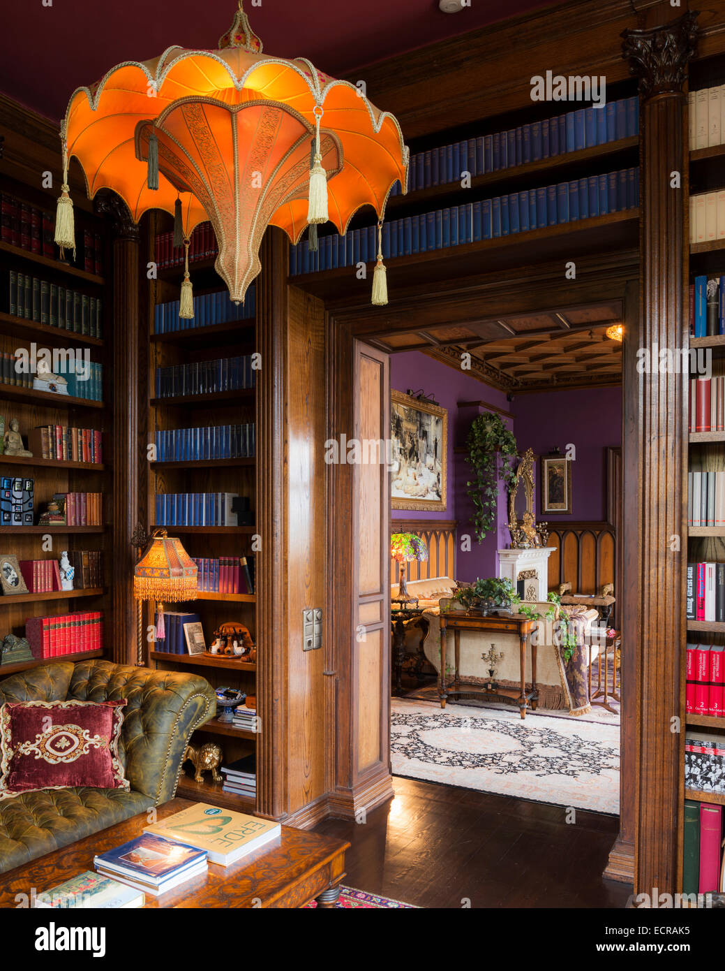 Parasol style lamp shade in castle library with buttoned leather sofa and coffee table - Stock Image