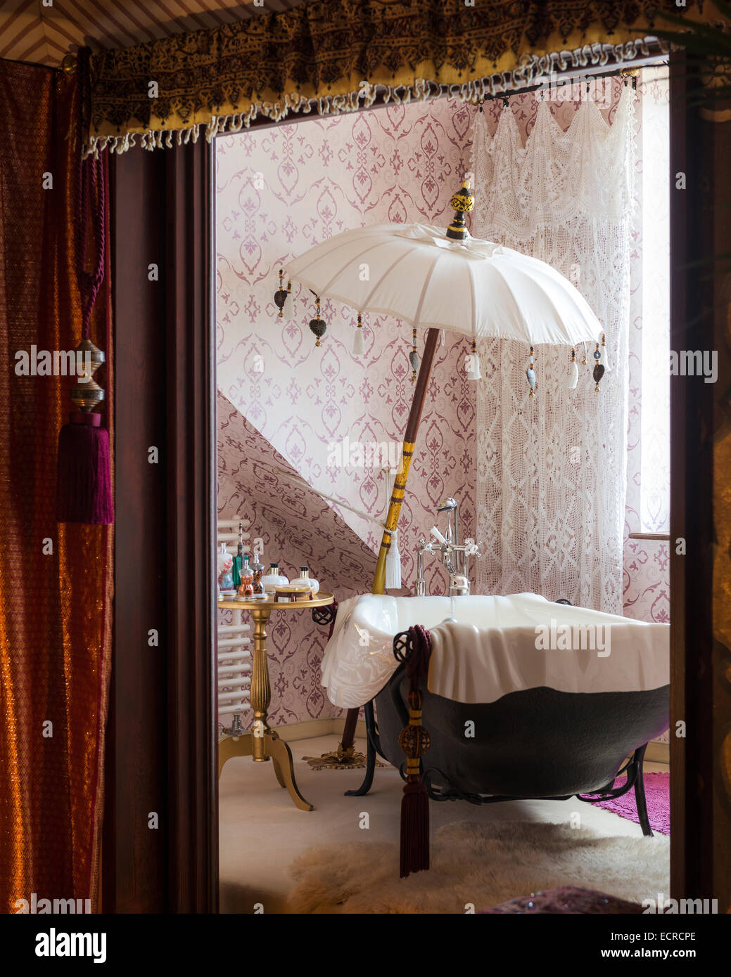 Free standing bath tub with parasol in bathroom with patterned wallpaper and net curtains - Stock Image