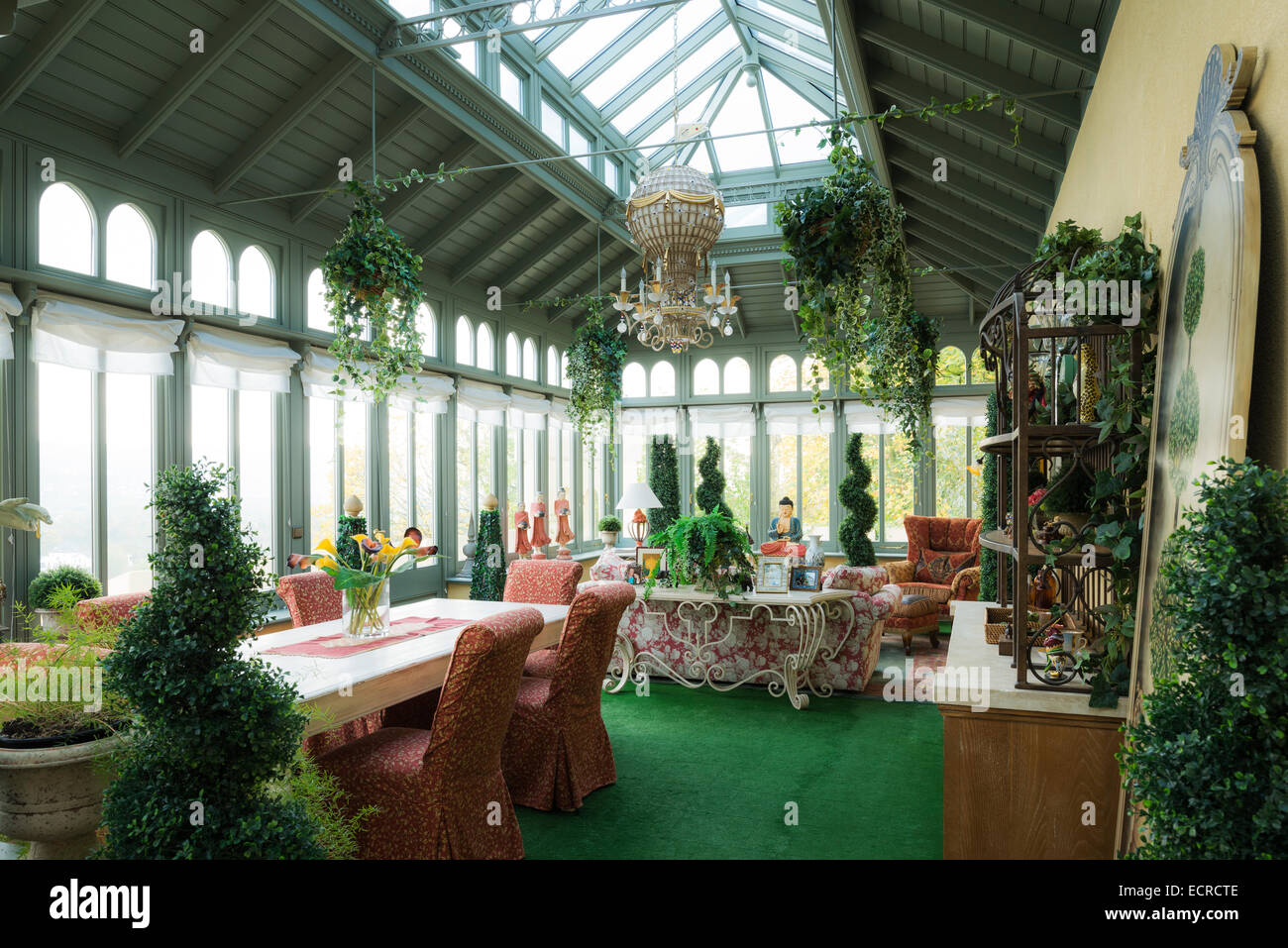 Green carpets and box hedge topiary in orangerie with dining area and floral sofa - Stock Image