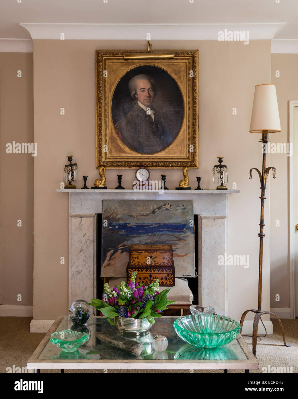 Gilt framed portrait above marble fireplace adorned with candle holders - Stock Image