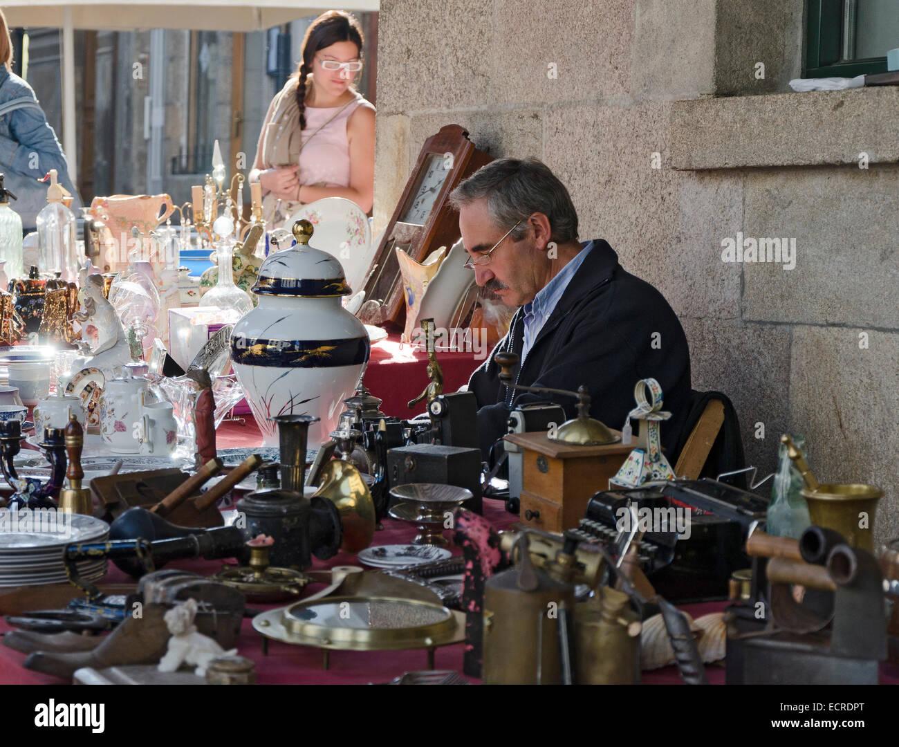 SANTIAGO DE COMPOSTELA, SPAIN – SEPTEMBER 8, 2012: A secondhand dealer sells stuff in a street market in Santiago - Stock Image
